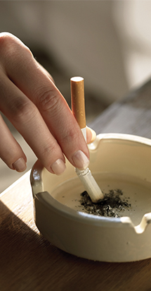 World No Tobacco Day: woman puts out her cigarette in an ashtray.