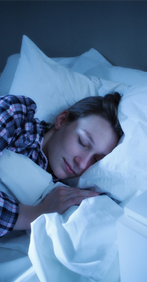 Woman sleeping comfortably in a bed to illustrate an sleeping patterns study.
