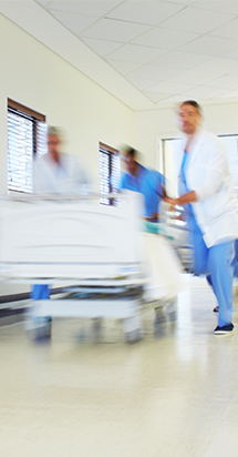 Surgeons run with a patient's bed along a hospital corridor.