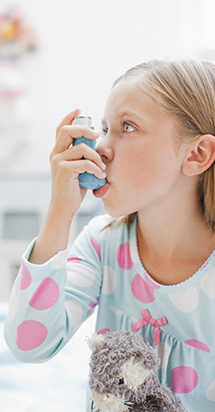 A young girl using an Asthma spray.