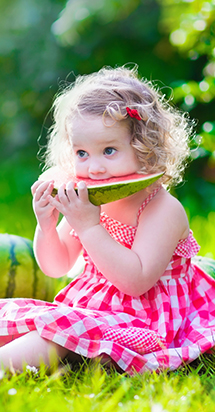 Small young girl eating watermelon to illustrate a nutritious and balanced diet.