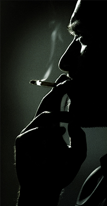 Smoking Cessation: man smoking a cigarette in a black background.
