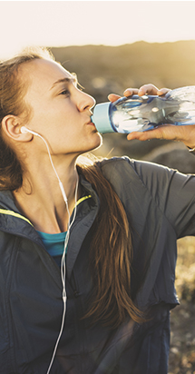 Young woman drinking water after jogging in a sunny scenery.