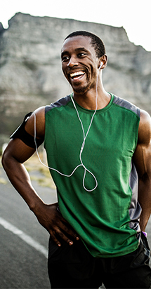 Happy black man jogging outdoors and with earphones to illustrate men's health.