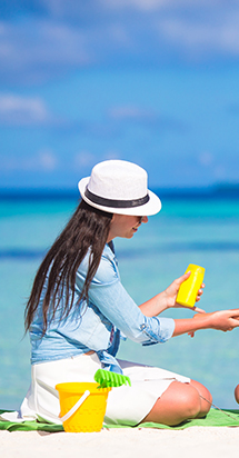 Expat mother puts sunscreen on her small daughter on the beach.