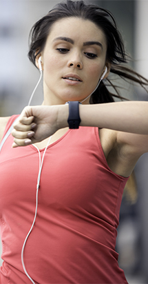 Fit woman jogging outdoors and looking at smartwatch.