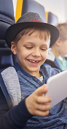 Young boy on plane playing with his tablet.