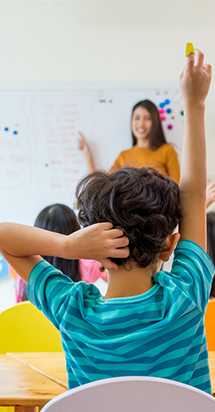 Young boy with his hand raised with his teacher is in the background pointing at the whiteboard.