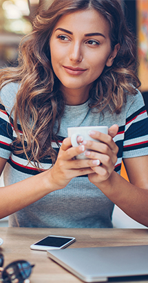 Young woman holding a cup with her both hands and having a relaxing time.