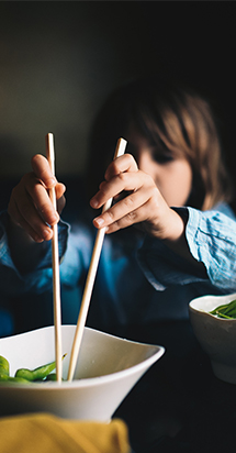 A happy child using chopsticks to eat his food.