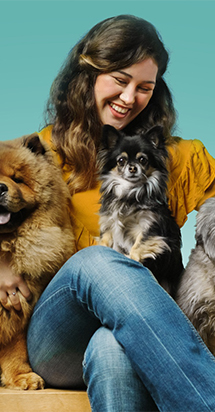A cheerful woman enjoying her moments smiling while holding three dogs in her lap.