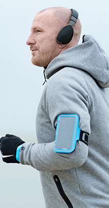 Middle-aged guy getting ready to exercise with his headphones on and mobile phone intact.