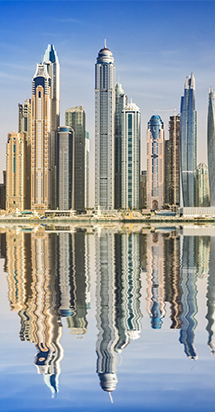 Riverside view of majestic skyscrapers mirroring its reflection on the shores of Dubai.