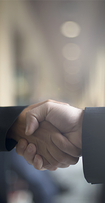 Front view of two business men shaking hands reaching an agreement.