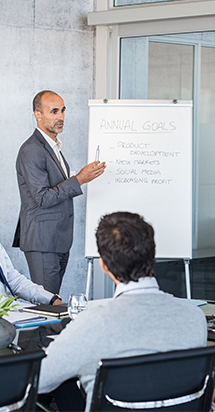 Senior businessman charting out the annual goals in a training session to expatriates.